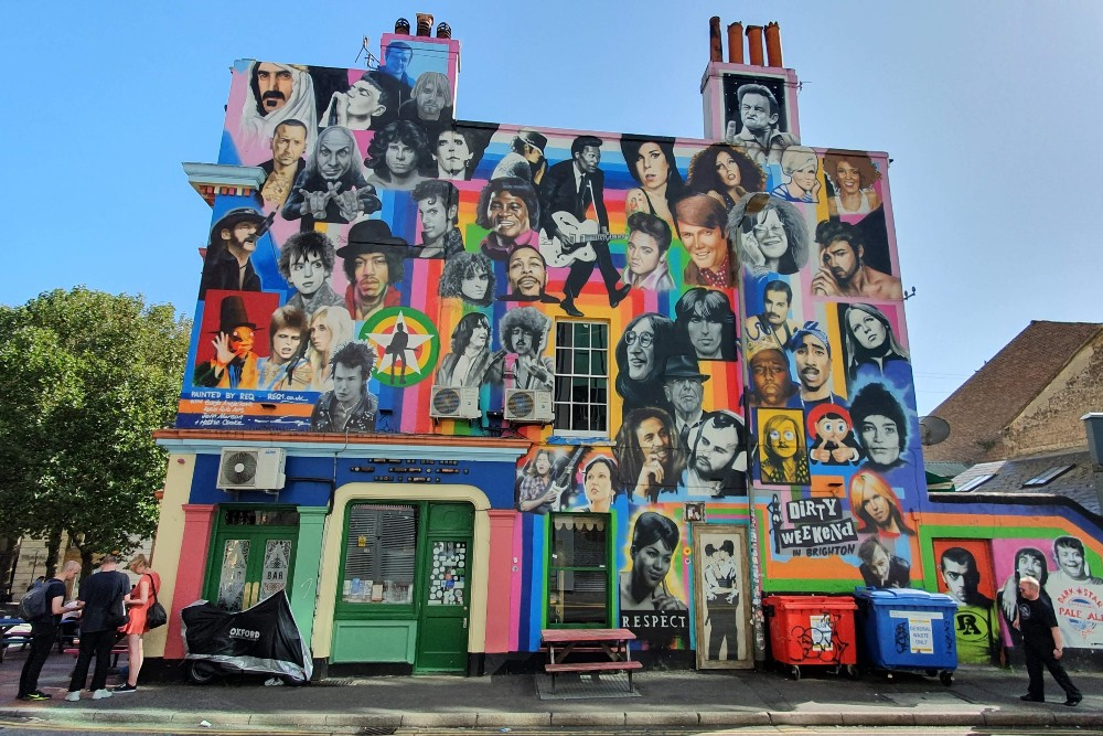 Street art a Brighton: murales con i volti della musica e The Kissing Coppers nel quartiere di North Laine in Inghilterra