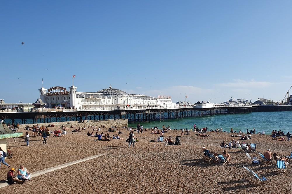 Veduta di Brighton Beach in Inghilterra con sdraio a righe e il Brighton Pier sullo sfondo
