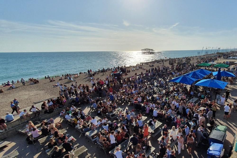 Persone sedute in spiaggia o ai tavoli dei locali di Brighton Beach sulla costa dell'Inghilterra