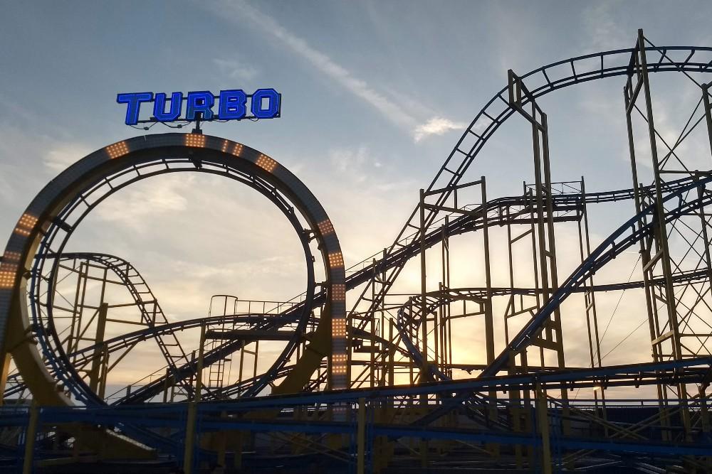 Tubo Coaster nel luna park del Brighton Palace Pier al tramonto