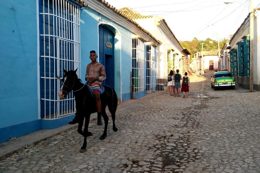 Viaggio a Cuba: vie acciottolate di Trinidad con case coloniali, macchine  colorate e cavalli
