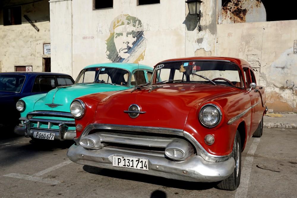 Auto colorate anni '50 nell'Habana Vieja a Cuba con il murales di Che Guevara sullo sfondo