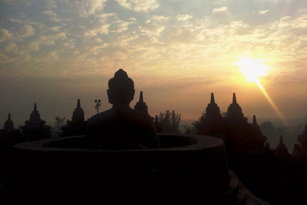 Tempio Borobudur in Indonesia: il sole che sorge illumina la statua di Buddha