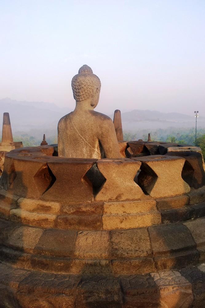 Statua di Buddha dentro uno stupa nel Tempio Borobudur in Indonesia