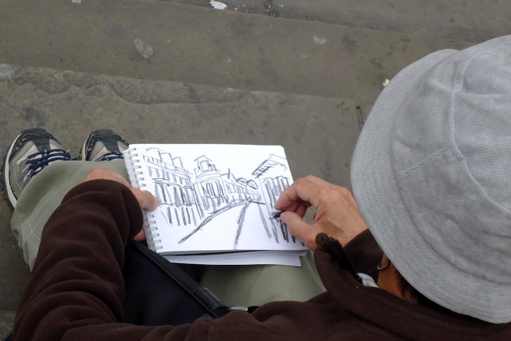 Artista che disegna seduto sui gradini della Statua di Eros a Piccadilly Circus a Londra