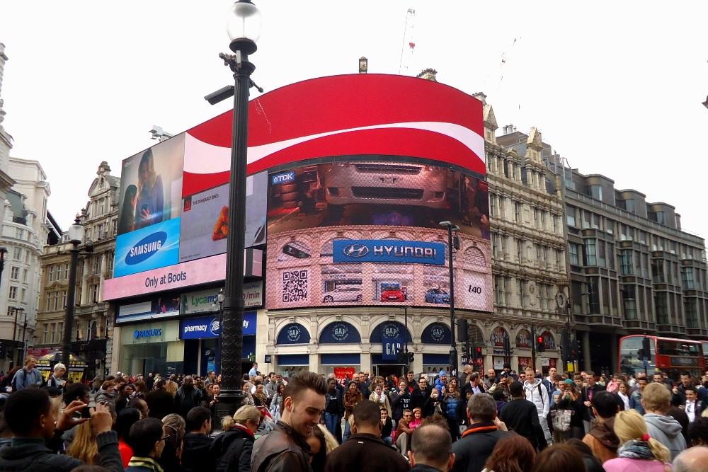 Persone e pannelli luminosi a Piccadilly Circus a Londra