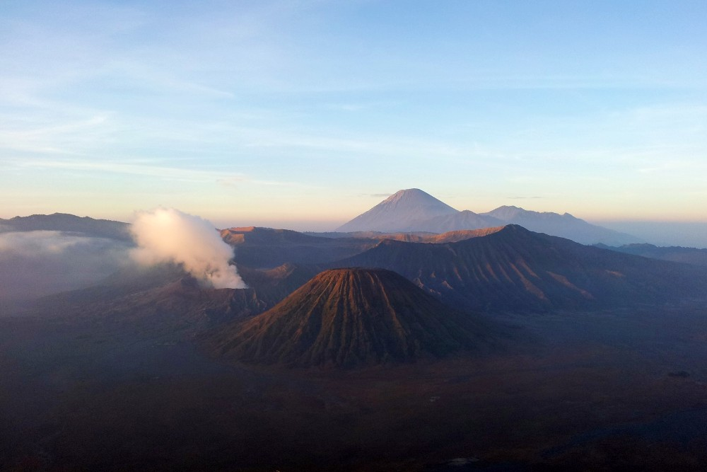 Vulcano Bromo fumante con le luci dell'alba sull'Isola di Giava in Indonesia