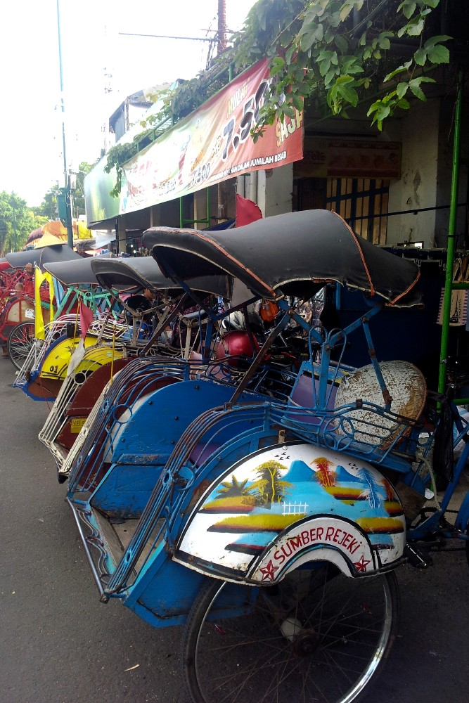 Becak colorati in fila per le strade di Yogyakarta sull'Isola di Giava