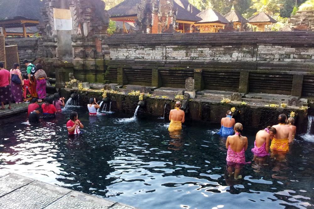 Viaggio a Bali: vasca con sorgenti sacre del Pura Tirta Empul, dove si immergono turisti e persone locali.