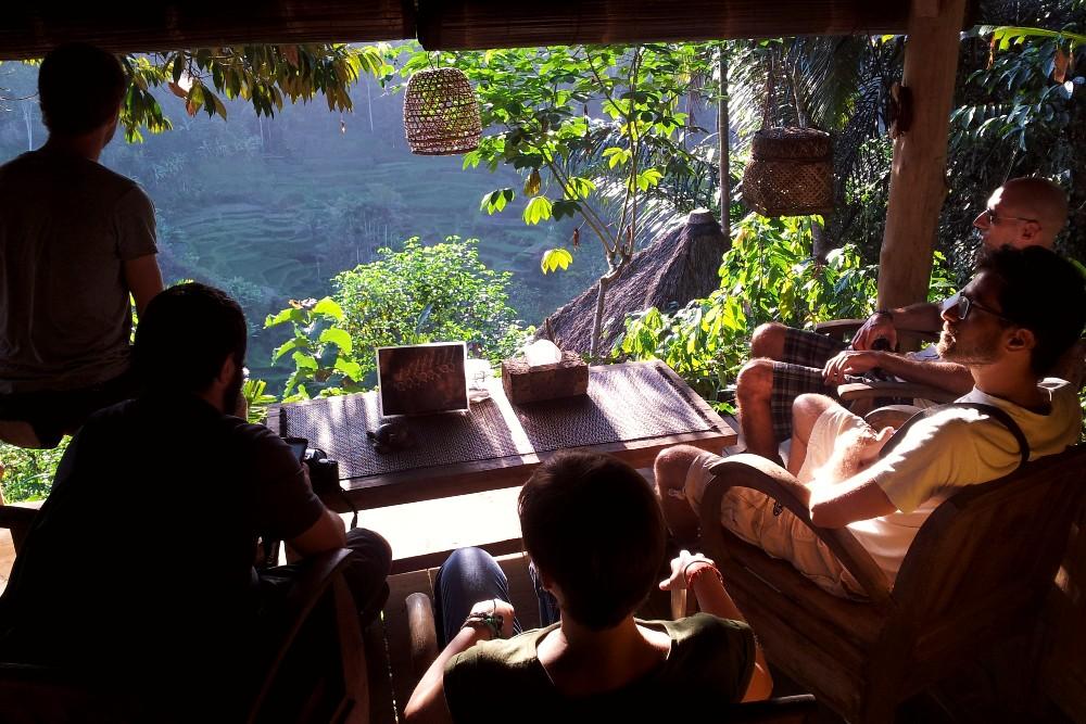 Gruppo di amici seduti sulla terrazza panoramica della piantagione di caffè Bali Pulina.
