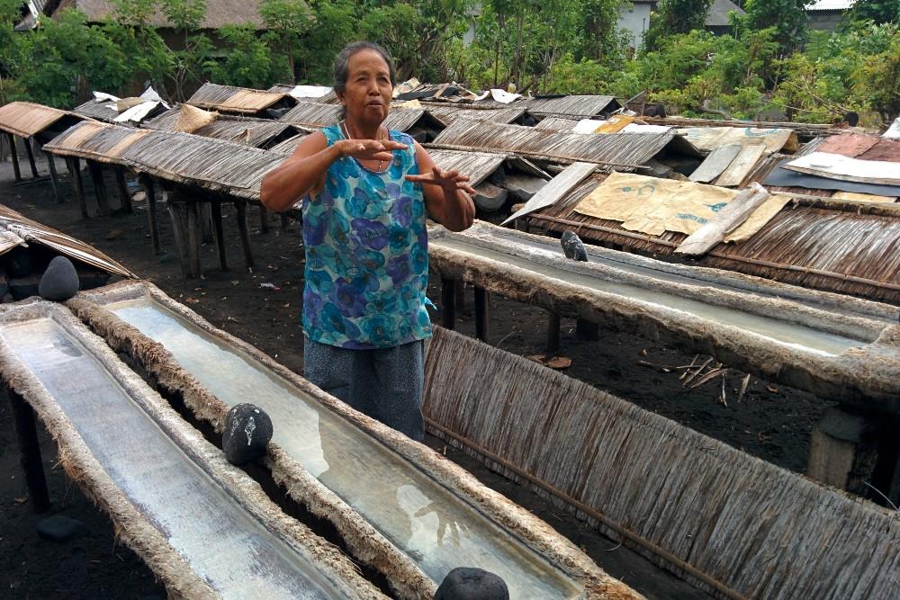 Signora che spiega la lavorazione del sale sulla spiaggia di Kusamba a Bali, Indonesia.