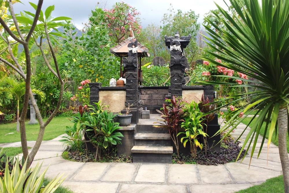 Giardino tropicale con un tempio induista alla Trijaya Guest House di Pamuteran a Bali.