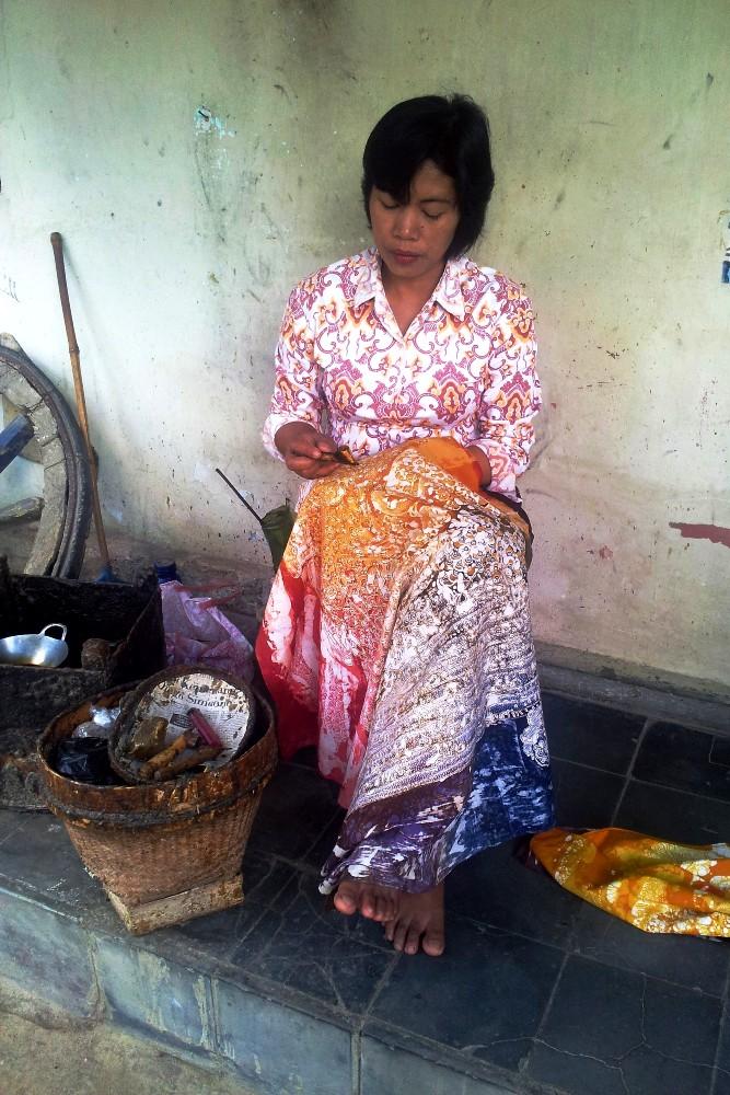 Donna indonesiana che applica la cera per realizzare un batik in una fabbrica di Yogyakarta.