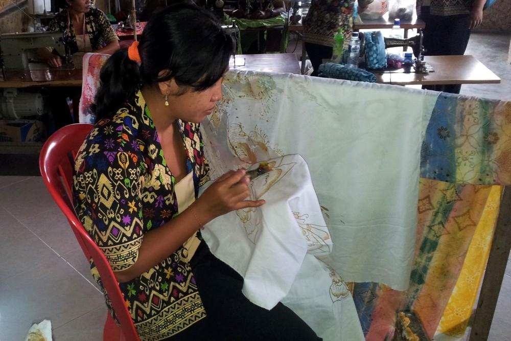 Donna indonesiana che applica la cera sul tessuto bianco durante il processo di produzione dei batik in una fabbrica di Bali.